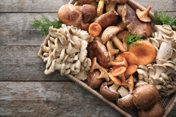 A basket of various uncooked mushrooms on a table.