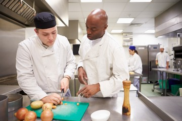 A chef teaching a student proper knife techniques.