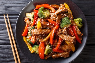 Asian teriyaki beef with bell pepper, broccoli and sesame close-up on a plate viewed from above.