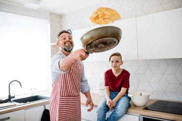 A father flipping a pancake into the air from his skillet as his sone watches on.