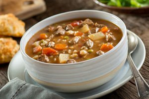A bowl of delicious beef and barley soup with carrots, tomato, potato, celery, and peas.