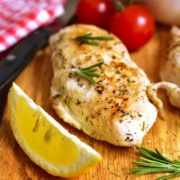 Grilled lemon rosemary chicken on a cutting board with fresh chopped rosemary and a juicy lemon wedge.