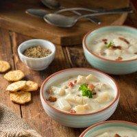 Three bowls of delicious homemade oyster stew on a table with crackers on the side.