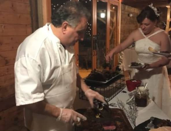 Chef Darren Maggio, a contributor for The Chefs Cooking School, carving roast beef at a wedding.